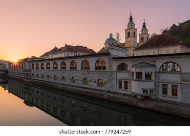 Ljubljanica river and Plecnik architecture on the river banks with Ljubljana Cathedral church and bell tower in the background in Ljubljana, Slovenia.
