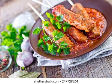 Ljulja-kebab with tomato sauce on the plate