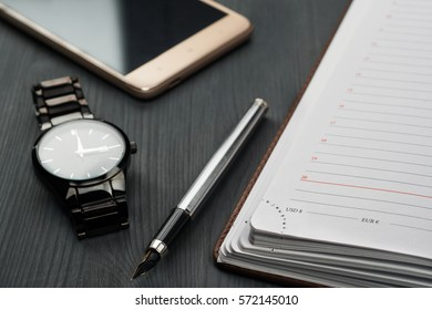 ll life, business, education concept. Office supplies, blank screen smartphone, gift box, watch, notepad, diary and pens on a table.