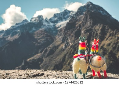 A llama-shaped key ring with the blurred  Andes mountain background.