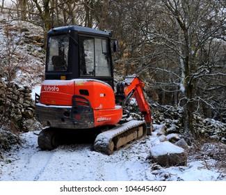 Llanbedr, Gwynedd, North Wales / UK - 02/28/2018: Kubota KX101-3a3 mini excavator parked at Rhaeadr Nantcol in the snow.