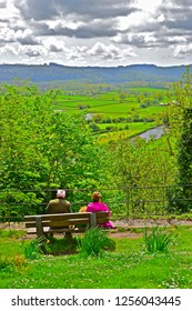 Llandeilo, Carmarthenshire / Wales UK - 5/10/2018: A couple sit admiring the beautiful views of the Welsh countryside with the river Towy meandering through rich farmland near Llandeilo in West Wales.