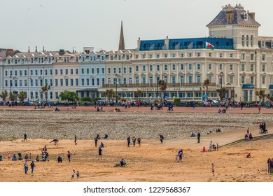 LLANDUDNO BAY,  WALES, UK, MAY 26TH, 2018 - North Shore Beach with it's Victorian buildings along the high street in Llandudno Bay, Wales.  People enjoying a weekend day along the beach.
