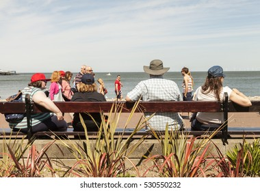 Llandudno, North Wales- 17th May 2014 : Family sitting on long wooden public bench  looking out to sea  on Llandudno promenade. From behind.
