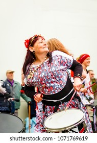 Llandudno, North Wales- 29th April 2017: Performers of the Batala Mersey carnival band  in Llandudno. Happy smiling woman in colorful outfit playing on a drum.