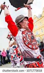 Llandudno, North Wales- 29th April 2017: Performers of the Batala Mersey carnival band  in Llandudno. Man in trilby fedora hat playing on a drum raised above his head.
