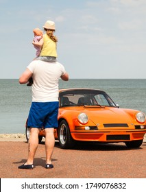 Llandudno, North Wales UK - May 18,, 2014: Farther with young daughter on his shoulders holding her doll tightly looking at a porch vintage car
