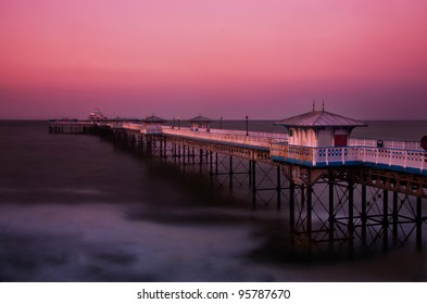 Llandudno pier at dusk with purple-red sky, North Wales