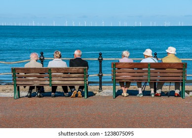 LLANDUDNO, UNITED KINGDOM - SEPTEMBER 05: People sitting watching the ocean on a waterfront promenade in the historic seaside town of Llandudno in Wales on September 05