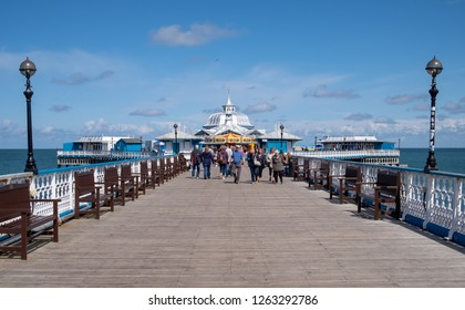 Llandudno, Wales, August 10, 2018  Summer holidayers on the wooden pier of Llandudno.  Brisk sunny day with some white puffy clouds.