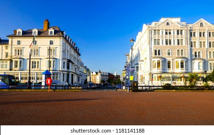 """Llandudno, Wales- August 31,2018: A picture of hotels and office in front of the seashore in North Wales during sunrise."""