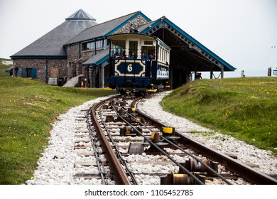 LLandudno, Wales, North Shore Beach, UK - MAY 27, 2018 Old blue vintage tramway leaving out the summit station. ride to the summit station An old funicular train with passengers moving on the railway