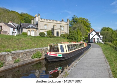 Llangollen Call, Llangollen, Denbighshire, Wales. 13th May, 2019.  A canal passenger boat passing in front of a large stone house on the Llangollen Canal with towpath & blue sky.