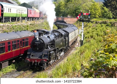 Llangollen, Denbighshire, Wales, 13th May, 2019. A steam engine Standard Class 4 Tank – 80072 in steam through a bridge with passenger carriages, passing a signal on the Llangollen Railway in Wales.