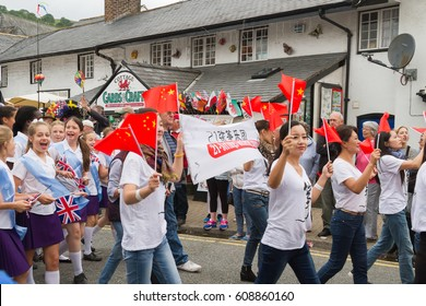 Llangollen Wales UK - July 7 2015: Chinese performers of the 21 string Guzheng Ensemble in the street parade at the start of the annual International Musical Eisteddfod in Llangollen