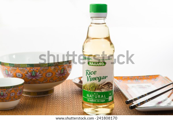 LLANO, TEXAS-Jan 05, 2015:   Bottle of Nakano Rice Vinegar on Bamboo place mat with Oriental Design Dishes as background.