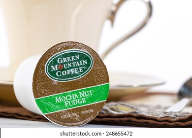 "LLANO, TEXAS-JAN 31, 2015: Selective focus on a Green Mountain Coffee Mocha Nut Fudge ""K-Cup"" for Keurig Brewers.  Elegant China dishes in soft background."