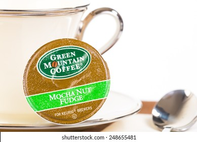 "LLANO, TEXAS-JAN 31, 2015: Selective focus on a Green Mountain Coffee Mocha Nut Fudge ""K-Cup"" for Keurig Brewers.  Elegant China dishes, white background, copy space."