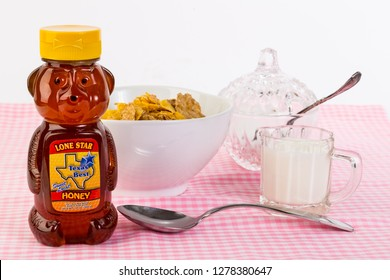 LLANO, TX, USA - MAY 03; Bear shaped bottle of Honey with bowl of cereal and cream.