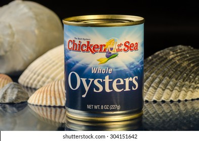 "LLANO, TX-AUG 07, 2015: Can of ""Chicken of the Sea"" Whole Oysters in front of various seashells against black background."