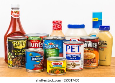 LLANO, TX-DEC 19, 2015: Canned and bottled groceries on food pantry shelf with white background and copy space.  Various Trademark brand names.