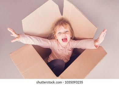 Llittle blonde girl screams inside a cardboard box. Toned
