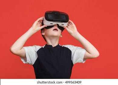 Llittle boy in 360 view virtual reality glasses playing the game on a red background. 3D gadget technology. Cardboard VR AR glasses