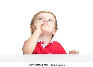 Llittle boy standing at white table looking up, isolated on a white background