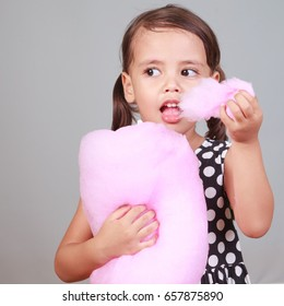 Llittle girl eating cotton candy.