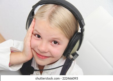 Llittle girl sits in front of a laptop with headphones and learning