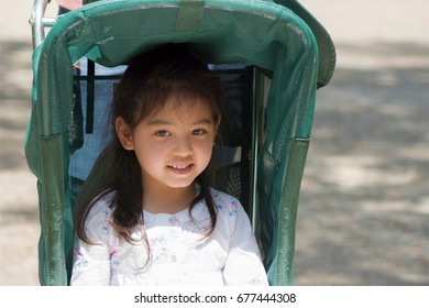 a llittle girl smiling and sitting in the stroller