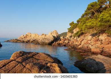 Lloret de Mar seascape. Coast of Mediterranean sea in Costa Brava, Spain. Scenery sea bay on clear summer day. Spanish resort. Rocky beach with stones on shore