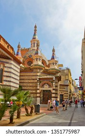 Lloret De Mar, Spain - April 27, 2018: Street with parish Church of Sant Romà and walking people