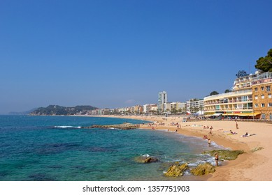 Lloret De Mar, Spain - April 27, 2018: People sunbathing on the small bay beach with promenade and hotels buildings on the background