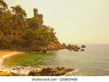 Lloret De Mar, Spain - April 27, 2018: Small bay beach with Castell d'en Plaja on the background