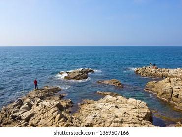 Lloret De Mar, Spain - April 27, 2018: Fishermen on the rocky shore of the Mediterranean
