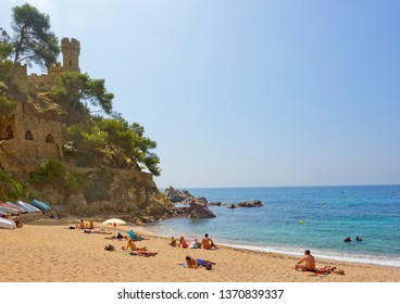 Lloret De Mar, Spain - April 27, 2018: People sunbathing on the small bay beach with Castell d'en Plaja on the background