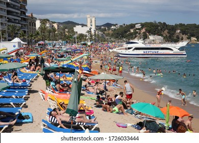 LLORET DE MAR, SPAIN, July 13, 2016: beach with a lot of people relaxing during summer. Big boat in a background for tourists people.
