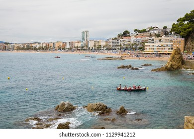 Lloret de Mar / Spain - June 27, 2018: Beach off the coast of Lloret de Mar, Costa Brava. People on the beach lie on sun loungers under umbrellas. Resting under a castle on the beach in the city.