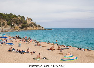 Lloret de Mar / Spain - June 27, 2018: Castell d'en Plajan on the Costa Brava and people on city beach in Lloret de Mar, Spain. Sand and sea waves.