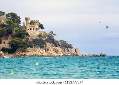 Lloret de Mar / Spain - June 27, 2018: Castell d'en Plajan on the Costa Brava and city beach in Lloret de Mar, Spain. Sand and sea waves.