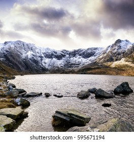 Llyn Idwal lake lying within Cwm Idwal in the Glyderau mountains of Snowdonia, Wales, UK. Snow covered peaks on a cold winter evening