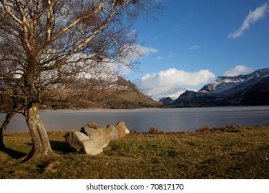 Llyn Nantlle Uchaf a frozen fishing lake in winter looking towards Snowdonia National park