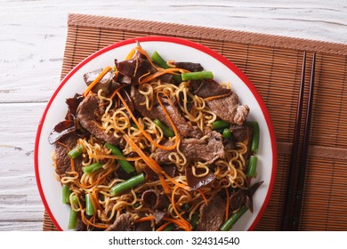 Lo mein with beef, muer and vegetables close-up on a plate. horizontal view from above