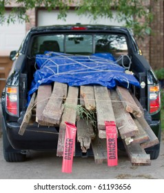"""load of lumber demolition debris in the bed of a pickup truck. Shallow depth of field with selective focus on the """"danger"""" flags on the back of the load."""