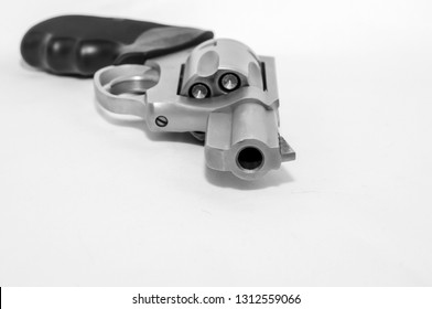 A loaded 357 magnum revolver on its side on a white background shown in black and white