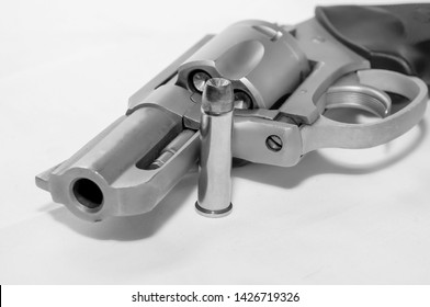 A loaded 357 stainless steel revolver with a hollow point bullet next to it shot in black and white