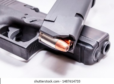 A loaded 9mm pistol magazine on top of a black 9mm pistol on a white background