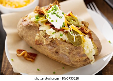 Loaded baked potato with bacon, cheese sour cream and chives