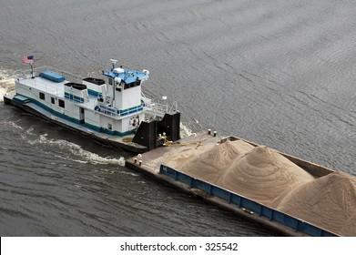 Loaded barge navigating the Mississippi River in St. Paul